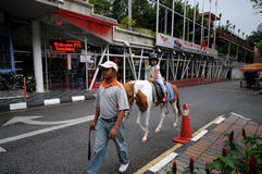 Girls ride horses in the vicinity of Kuala Lumpur tower Stock Photography
