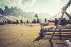 Girls ride on a swing. Happy fun  life. Girl swinging on a swing in the park  Puez Odle. Italy stock photos
