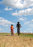 Girls riding bicycle. Two small girls riding bicycle Stock Images