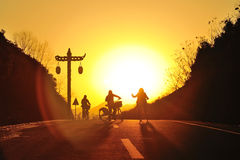 Girls riding bicycle on the sunset. Silhouette young girls riding bicycle on the sunset royalty free stock image
