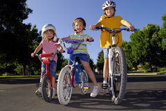 Girls Riding Bikes. Sisters riding bikes together and laughing Royalty Free Stock Images