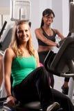 Girls riding exercise bikes Stock Photos
