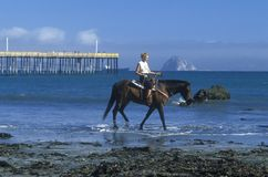 Girls riding horseback on beach, Morro Bay, CA Royalty Free Stock Photos