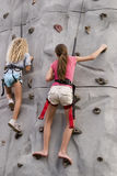 Girls rock climbing 2. Two girls rock climbing in safety harnesses Stock Photography