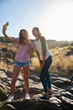 Girls on a rock taking selfies Royalty Free Stock Images