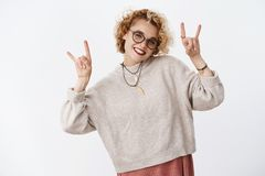 Girls rock this world. Charismatic excited and joyful attractive european woman with short blond curly hairstyle in. Glasses and hipster necklace showing rock-n royalty free stock images