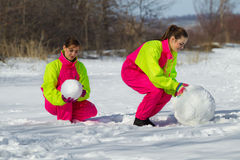 Girls rolling a huge snowbal Stock Image