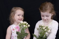 Girls and roses. Sisters with fresh roses Royalty Free Stock Photo