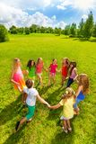 Girls roundelay. Large group of happy girls play roundelay and stand in circle in the park on the green grass on sunny summer day top view Royalty Free Stock Photos