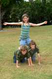Girls rule. A happy smiling group of three youth outdoors making a pyramid with young girl on the top Stock Photo