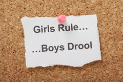 Girls Rule Boys Drool. The phrase Girls Rule Boys Drool typed on a piece of paper and pinned to a cork notice board stock photography