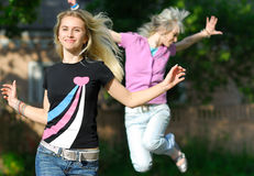 Girls run. Two young beautiful women run on road and laugh Royalty Free Stock Photography