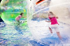 Girls Run in Floating Balls. Two young girls playing inside a floating water walking ball royalty free stock photos