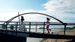 Girls run over the bridge on the sandy beach. Hair fluttering, the sun is shining, blue sky. Youth at seaside in slow motion. Friends having fun happy relax stock video footage