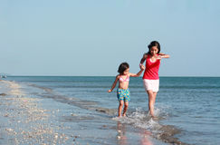 Girls running along the beach Royalty Free Stock Image