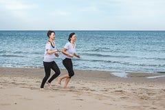 Girls running around the beach stock images