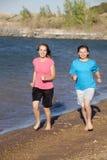 Girls running on beach Stock Images
