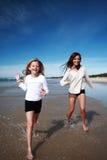 Girls running on beach stock photography
