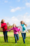 Girls running through fall or autumn park Stock Image