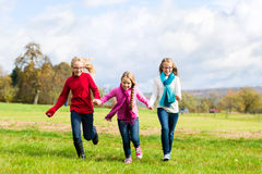 Girls running through fall or autumn park Stock Images