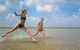 Girls running and jumping above the water stock photo