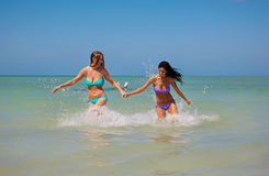 Girls running out of water Royalty Free Stock Photo