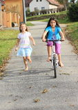 Girls running and riding a bike royalty free stock photos