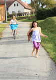 Girls running and riding a bike Royalty Free Stock Images