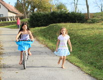 Girls running and riding a bike Stock Photos