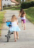 Girls running and riding a bike Royalty Free Stock Photography