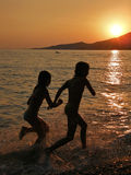 Girls running at sea. Silhouettes of two young girls - best friends run into the shallows of the Adriatic Sea in the beautiful sunset. Around them, the sea foam Stock Images