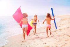 Girls running with swimming tools along the sea Stock Photos