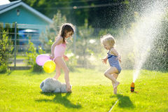 Girls running though a sprinkler in a backyard Stock Image