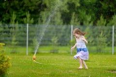 Girls running though a sprinkler Stock Photo