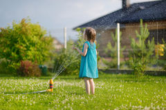 Girls running though a sprinkler Royalty Free Stock Images