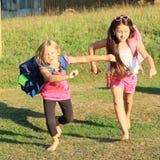 Girls running to school. Happy barefoot girls going back to school Stock Photos