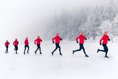 Girls running together on snow in winter mountains. Sport, fitness inspiration and motivation. Happy group of women trail running stock image