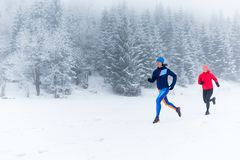 Two women trail running on snow in winter mountains. Girls running together on snow in winter mountains. Sport, fitness inspiration and motivation. Two women Stock Images