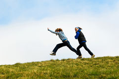 Girls running on top of hill Royalty Free Stock Photography