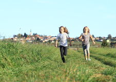 Girls running from village Royalty Free Stock Image