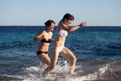 Girls runs on sea wave Stock Photos