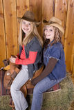Girls on saddle smiling Royalty Free Stock Photo