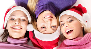 Girls in santa hat lying head next to head. Royalty Free Stock Image