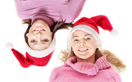 Girls in santa hat lying head next to head. Stock Photography