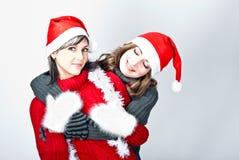 Girls in Santa's caps Stock Images