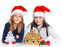 Girls in Santa's hat with gingerbread house Stock Photo