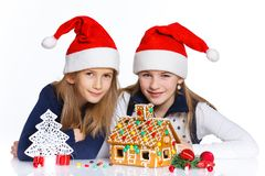 Girls in Santa's hat with gingerbread house Stock Photos