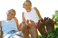 Girls sat on grass in summer. Two smiling young girls sat on grass in summer scene, focus on their bare feet Royalty Free Stock Photography