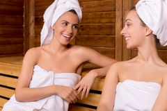 Girls in sauna. Two attractive women wrapped in towel talking to each other and smiling while relaxing in sauna stock images