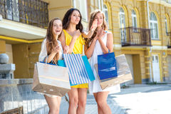 Girls saw the new shop. Girls holding shopping bags and walk aro Stock Image